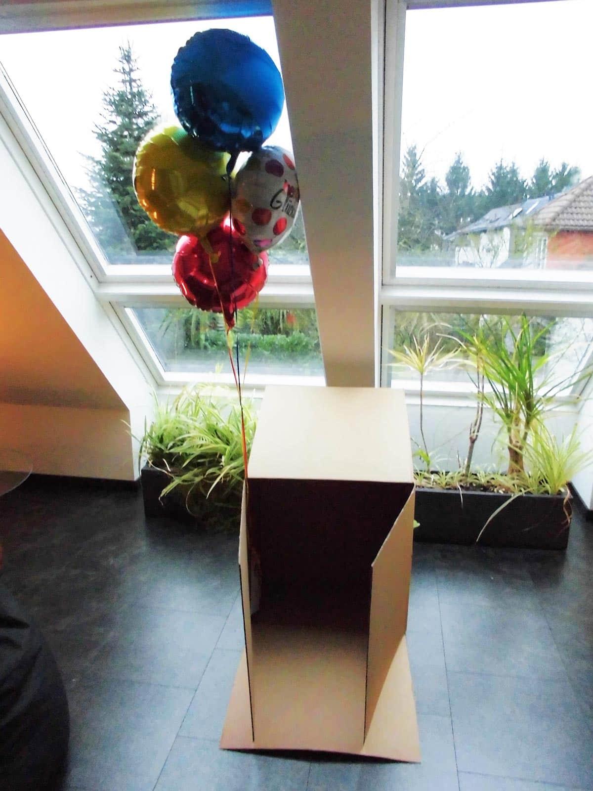 Die Geschenkballons sind mit Tesafilm am Pappkarton festgeklebt