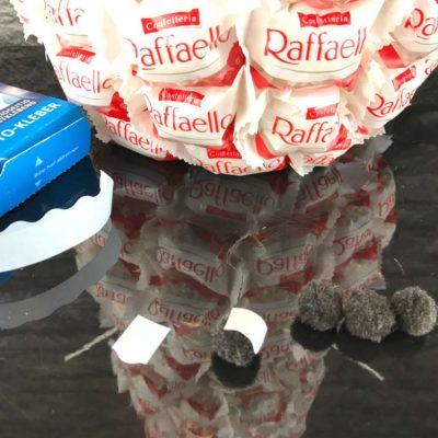 Die schwarzen Mini Pompons dienen als Knöpfe und werden mit selbstklebenden Foto-Tapes am Rafaello Schneemann befestigt