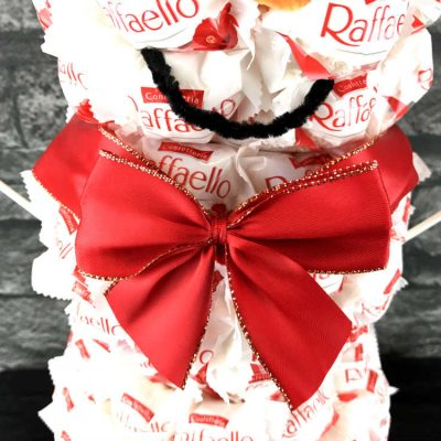 Eine Geschenkschleife ersetzt den Schal des Schneemanns