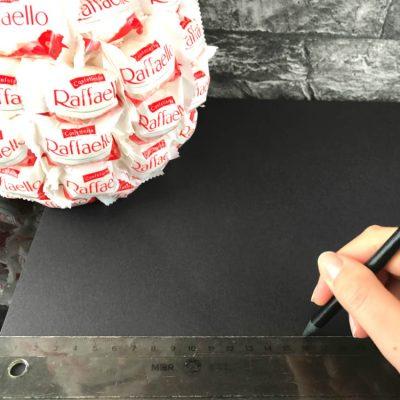 Male für den Schneemann Hut ein Quadrat auf schwarzen Tonkarton auf